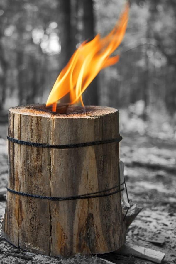 Burning Swedish candle of log on a black and white background. Handmade tourism