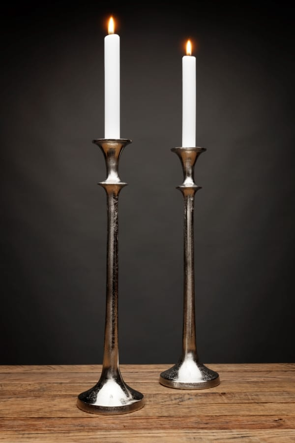 2 tall silver candle holders and glowing candles, shot on a wooden table