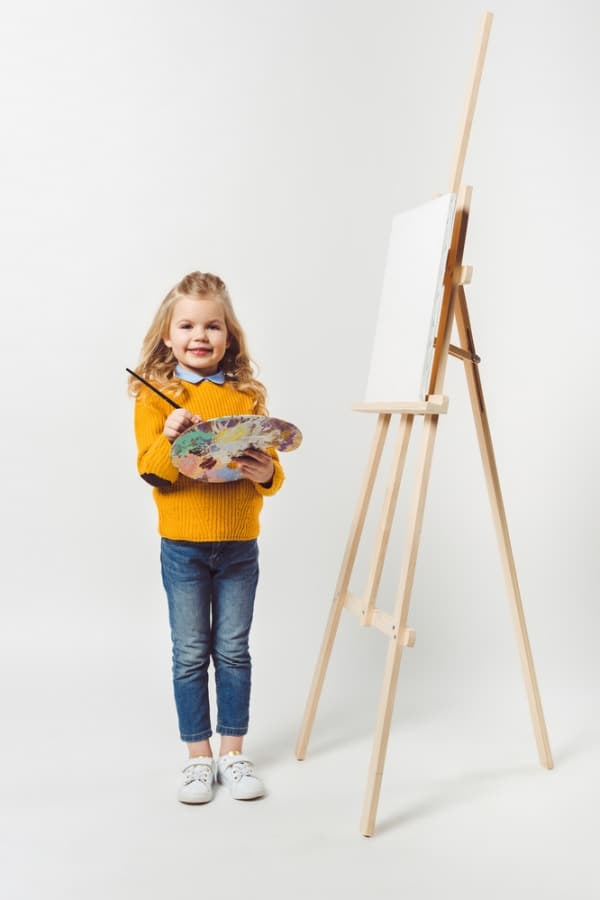 child with paint brush on a canvas