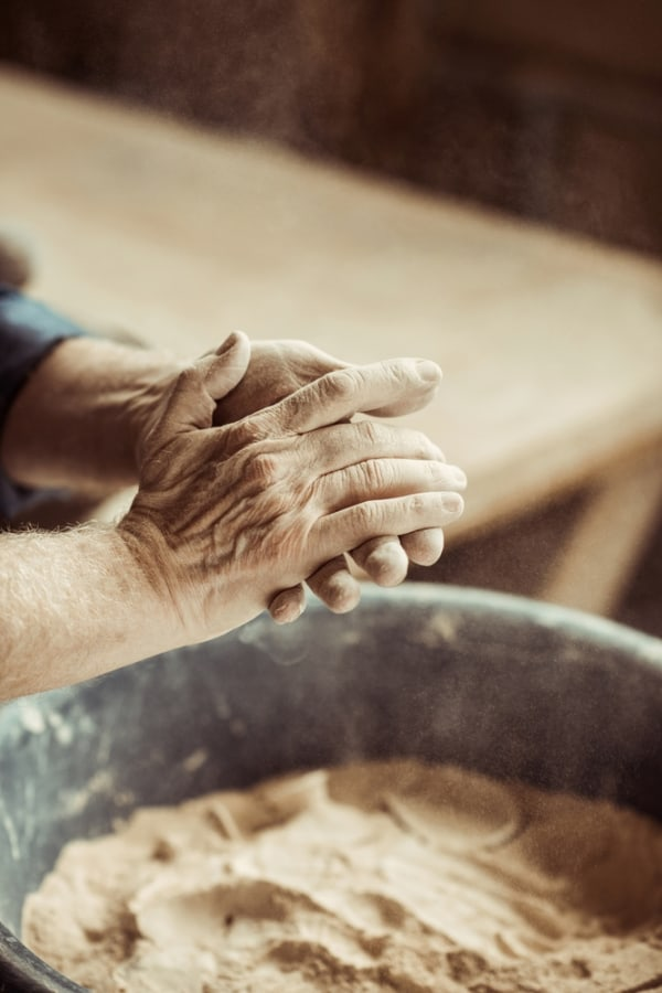 potter hands taking clay from a bowl